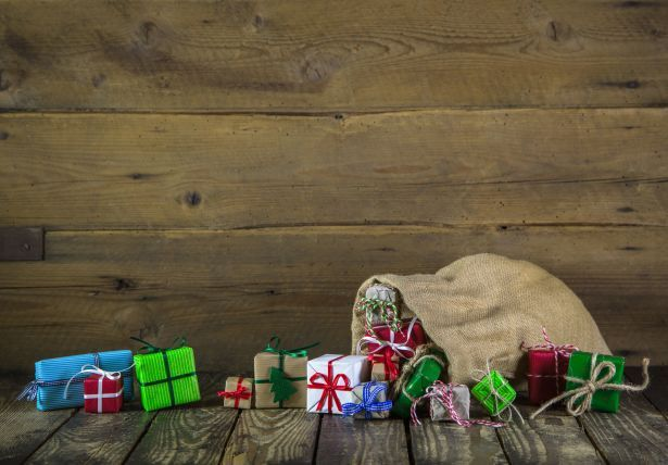 christmas presents in burlap bag wooden background